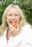 Mature woman biting apple Royalty Free Stock Photography
