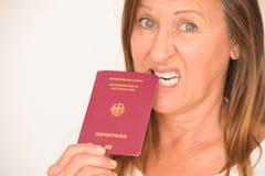 Mature woman biting German passport Royalty Free Stock Image