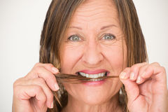 Mature woman biting split ends hair Royalty Free Stock Photos