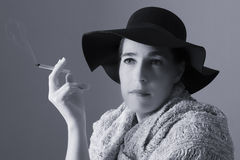 Mature woman with black hat sit smoking Royalty Free Stock Photography