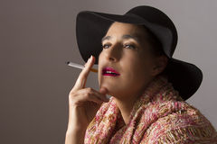 Mature woman with black hat sit smoking Stock Photography