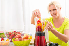 Mature woman blending a smoothie Royalty Free Stock Photos
