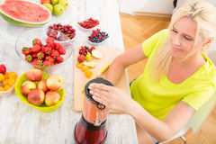 Mature woman blending a smoothie Stock Images