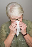Mature woman blowing her nose. An elderly woman blowing her nose in tissue paper Stock Photos