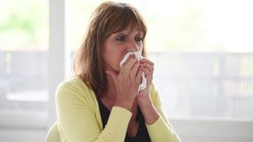 Mature woman blowing her nose stock video