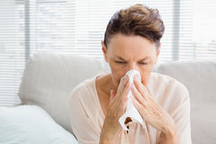 Mature woman with blowing nose. While sitting on sofa at home Stock Images