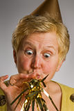 Mature woman blowing party horn Stock Photography