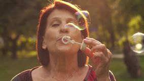 Mature woman blowing soap bubbles stock video footage
