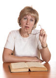 The mature woman with  book behind a table Stock Images