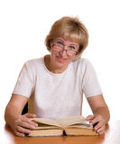 The mature woman with  book behind a table Royalty Free Stock Photos
