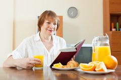 Mature woman with book during breakfast Royalty Free Stock Photo