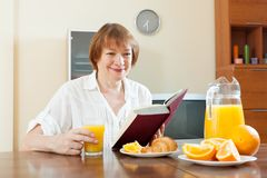 Mature woman with book during breakfast Stock Photos