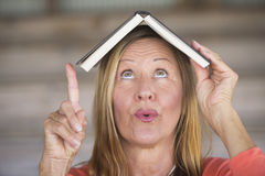 Mature woman with book on head and idea Royalty Free Stock Photography