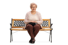 Mature woman with book in her lap sitting on bench Royalty Free Stock Photography