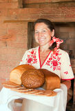 Mature woman with bread near  russian stove Stock Photo