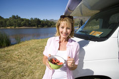 Mature woman with breakfast bowl by motor home and lake, smiling, portrait Royalty Free Stock Photo