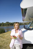 Mature woman with breakfast bowl by motor home and lake, smiling, portrait Royalty Free Stock Image