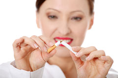 Mature woman breaking cigarette Royalty Free Stock Photography