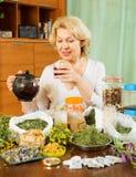 Mature woman brewing herbs Stock Photo