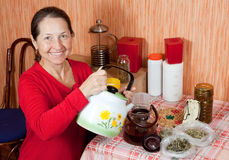 Mature woman brews herbs Stock Photo