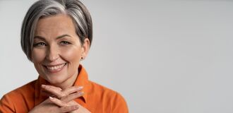 Free Mature Woman Broadly Smiling With Fingers Crossed. Happy Female Model In Orange Shirt. Close Up Portrait. Maturity Stock Photo - 190046200