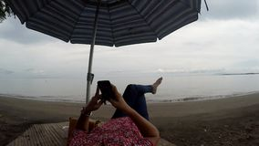 Mature woman browses internet with the use of mobile smartphone while lying cross legged under parasol sunshade on tropical beach. Tracking shot stock video