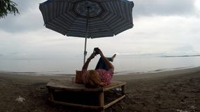 Mature woman browses internet with the use of mobile smartphone while lying cross legged under parasol sunshade on tropical beach. Tracking shot stock video footage