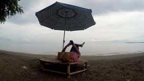 Mature woman browses internet with the use of mobile smartphone while lying cross legged under parasol sunshade on tropical beach. Tracking shot stock footage