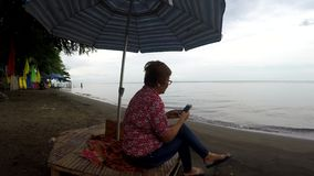 Mature woman browses internet with the use of mobile smartphone while sitting cross legged under parasol sunshade. On tropical beach. tracking shot stock video footage