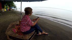 Mature woman browses internet with the use of mobile smartphone while sitting cross legged under parasol sunshade. On tropical beach. tracking shot stock footage