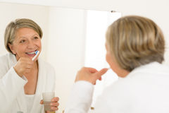 Mature woman brushing teeth look bathroom mirror Royalty Free Stock Photography