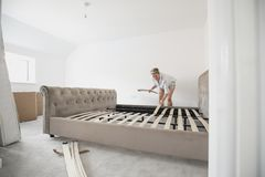 Mature Woman Building Bed in New Home Royalty Free Stock Photos