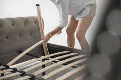 Mature Woman Building Bed in New Home Stock Images