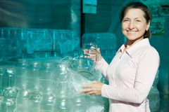 Mature woman buying glass cans. At warehouse Royalty Free Stock Photo