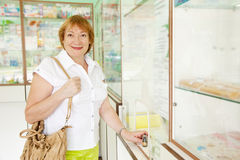 Mature woman buys drugs Royalty Free Stock Photography