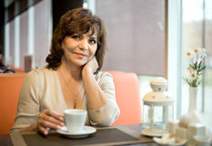 Mature woman in Cafe. Very beautiful, mature woman, sit in  Cafe and drink coffee, horizontal portrait Stock Images