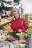 Mature Woman On Call While Grocery Shopping Royalty Free Stock Photo