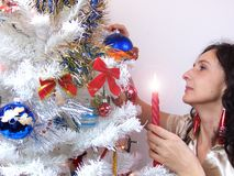 Mature woman with candle decorating Christmas tree Royalty Free Stock Photo