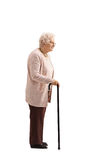 Mature woman with a cane waiting in line. Full length profile shot of a mature woman with a cane waiting in line isolated on white background Royalty Free Stock Photos