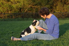 Mature woman and canine friend. Mature woman and spaniel sitting in park Royalty Free Stock Photos
