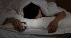 Mature woman cannot sleep at night time. Woman with insomnia, under blanket looking down, holding alarm clock in hand. Select light and focus on woman and clock stock photo