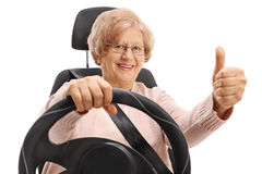 Mature woman in car seat making thumb up sign Stock Photos