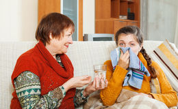Mature woman caring for  adult daughter has cough. Mature women caring for  adult daughter has cough in living room. Focus on girl Royalty Free Stock Image