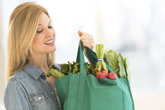 Mature Woman Carrying Shopping Bag Full Of Vegetables. Happy mature woman carrying shopping bag full of vegetables at home Royalty Free Stock Photos