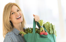 Mature Woman Carrying Shopping Bag Full Of Vegetables. Portrait of happy mature women carrying shopping bag full of vegetables at home Royalty Free Stock Image