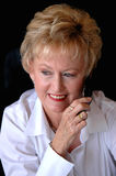 Mature woman on cell phone. An older smiling business woman on a cell phone looking away Royalty Free Stock Images