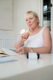 Mature woman checking bills and doing budget stock images