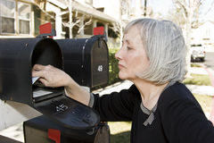 Mature Woman Checking Mailbox. An attractive mature woman is removing mail from her mailbox Royalty Free Stock Photos