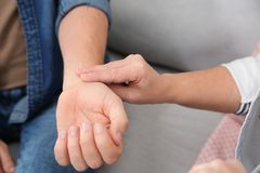 Mature woman checking man`s pulse with fingers indoors. Closeup royalty free stock image