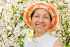 Mature woman with cherry blossoms. Portrait of beautiful mature woman in spring garden stock image